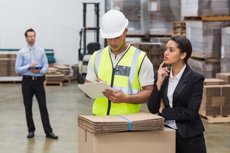 Warehouse manager and worker talking in a large warehouse photo