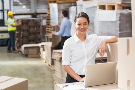 Smiling warehouse manager using laptop in a large warehouse Stock Photo