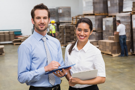 warehouses: Smiling warehouse managers working together in a large warehouse