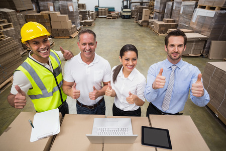 thumbs up gesture: Warehouse team smiling at camera showing thumbs up in a large warehouse Stock Photo