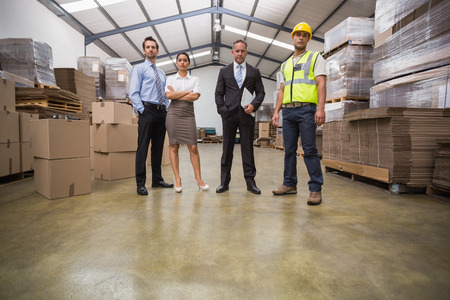 manual job: Warehouse team standing looking at camera in a large warehouse Stock Photo