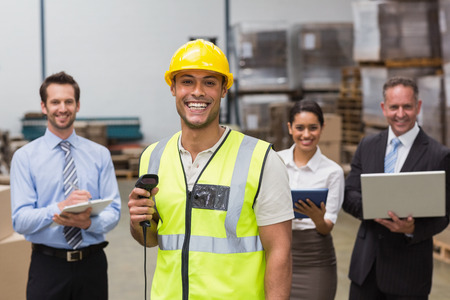 Worker standing with scanner in front of his colleagues in a large warehouse photo