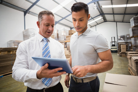 warehouse: Warehouse manager using tablet pc with colleague in a large warehouse Stock Photo