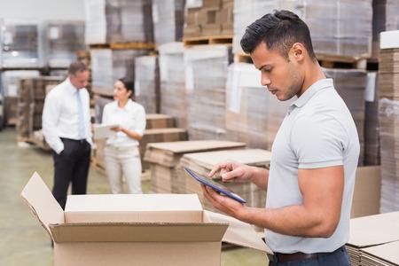 inventario: Retrato de gerente masculino que usa la tableta digital en almac�n