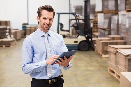 man using computer: Portrait of male manager using digital tablet in warehouse