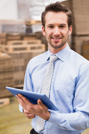 warehouse worker: Portrait of male manager using digital tablet in warehouse