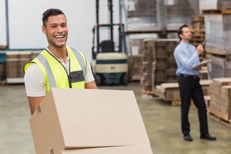 warehouse: Smiling warehouse worker moving boxes on trolley in a large warehouse