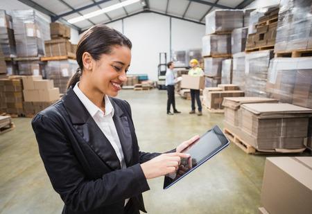 industriales: Encargado de sexo femenino que usa la tableta digital en almac�n