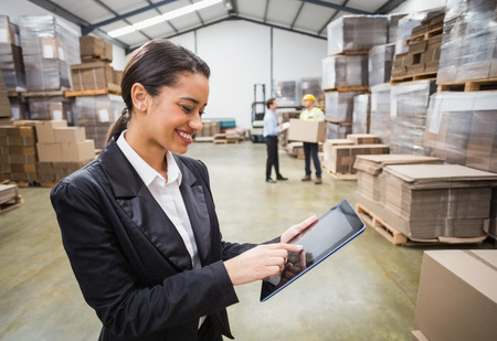 inventories: Female manager using digital tablet in warehouse