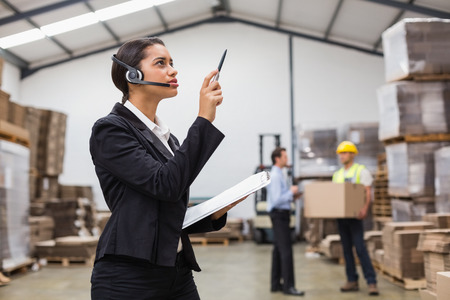 distribution warehouse: Warehouse manager wearing headset checking inventory in a large warehouse Stock Photo