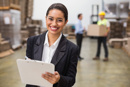 young adult men: Smiling warehouse manager writing on clipboard in warehouse Stock Photo