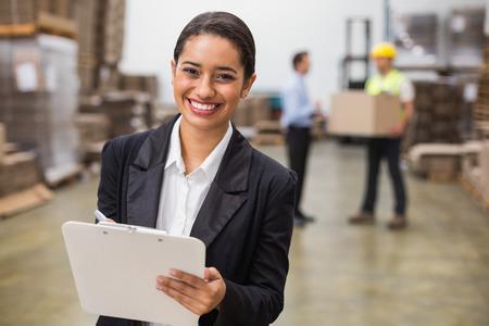 hombre escribiendo: Sonriendo gerente de almac�n escrito en el portapapeles en almac�n Foto de archivo