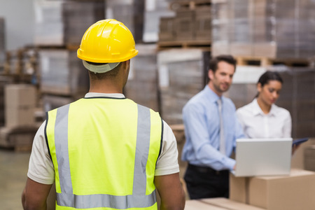 warehouse worker: Rear view of warehouse worker in front of his managers in a large warehouse Stock Photo