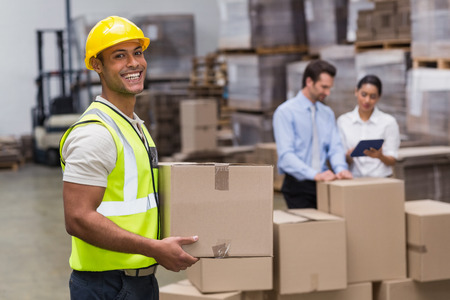 warehouse worker: Portrait of worker carrying box in the warehouse