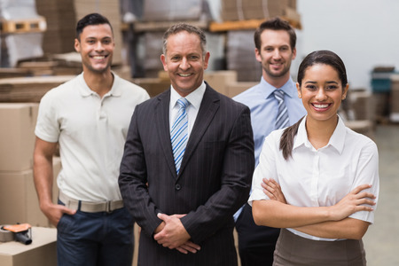 casual attire: Warehouse team smiling at camera in warehouse Stock Photo