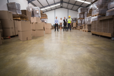 communication industry: Warehouse managers and worker talking together in a large warehouse