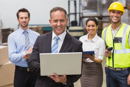 Smiling boss using laptop in front of his employees in a large warehouse photo