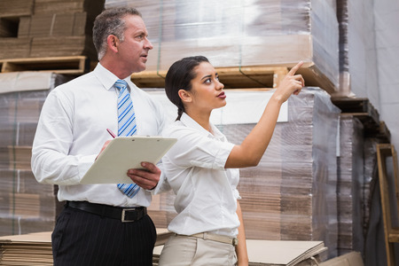 Warehouse manager and her boss checking inventory in a large warehouse photo