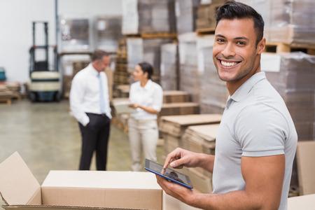 Glimlachende manager die digitale tablet in het magazijn