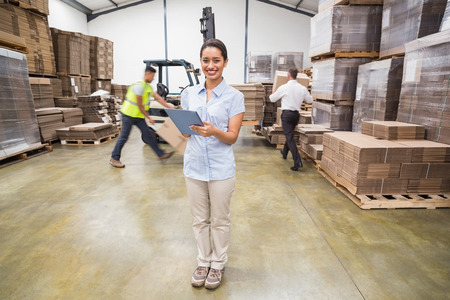 Smiling manager using digital tablet during busy period in a large warehouse Stock Photo
