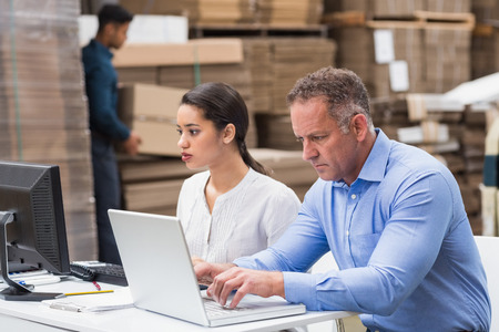 warehouse: Warehouse managers working with laptop at desk in a large warehouse Stock Photo