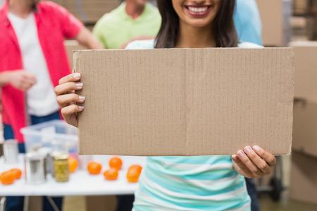 altruismo: Close up de voluntarios que muestra un cartel en un gran almac�n Foto de archivo