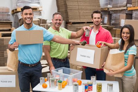 altruismo: Trabajadores del almac�n de embalaje, cajas de donaci�n en un gran almac�n