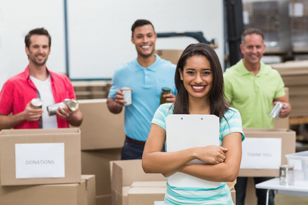 young caucasian: Smiling young female volunteer holding clipboard in a large warehouse