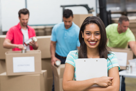 Smiling young female volunteer holding clipboard in a large warehouse