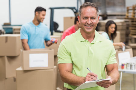 give charity: Smiling volunteer man taking notes holding clipboard in a large warehouse Stock Photo
