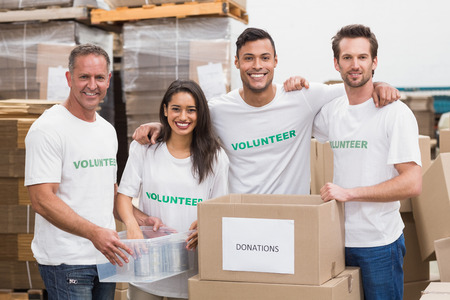 Team of volunteers smiling at camera in a large warehouse Stok Fotoğraf
