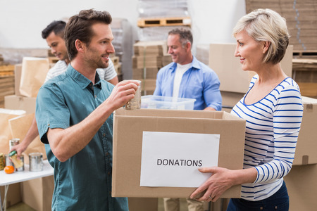 Two volunteers holding a donations box in a large warehouse