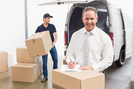 warehouse: Smiling manager standing behind stack of cardboard boxes in a large warehouse Stock Photo