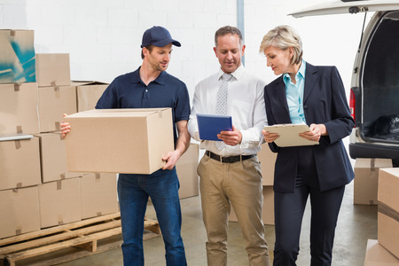 Delivery driver checking his list on tablet with managers in a large warehouse Stock Photo
