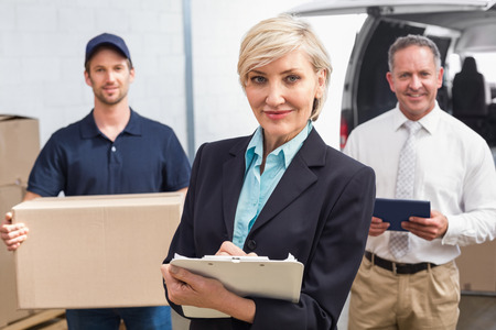 female worker: Smiling manager holding clipboard in front of his colleagues in a large warehouse Stock Photo