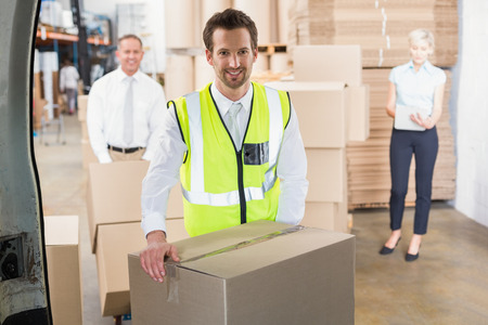 loading bay: Delivery driver loading his van with boxes outside the warehouse Stock Photo