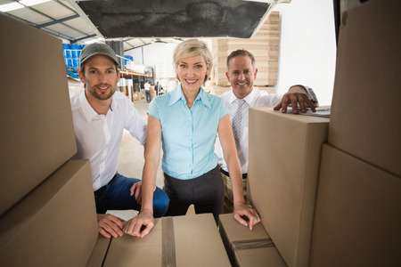 young man smiling: Portrait of managers smiling at camera behind the van in a large warehouse Stock Photo