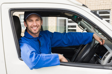 transportation: Delivery driver smiling at camera in his van outside the warehouse Stock Photo