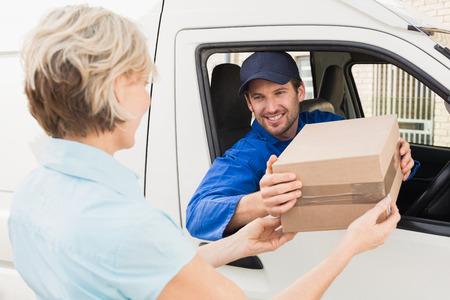 Livreur remise colis au client dans sa camionnette extérieur de l'entrepôt