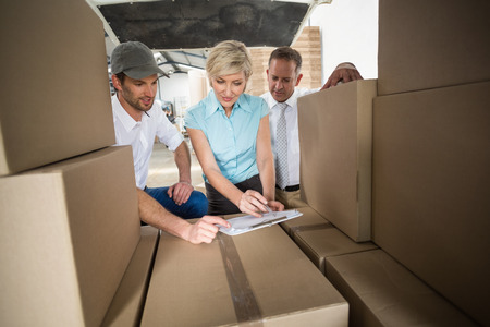 woman boss: Warehouse team working together with clipboard in a large warehouse
