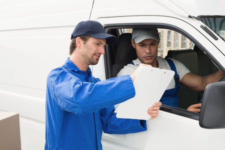 loading bay: Delivery driver showing customer where to sign outside the warehouse Stock Photo