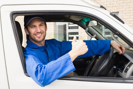 overalls: Delivery driver smiling at camera in his van outside the warehouse Stock Photo