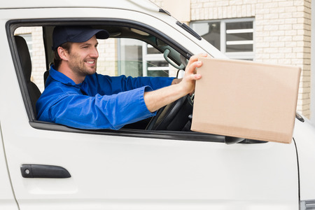 loading bay: Delivery driver offering parcel from his van outside the warehouse Stock Photo