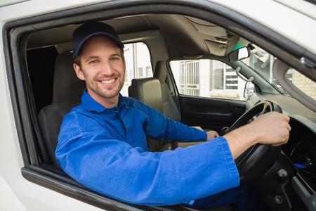 Livreur souriant à la caméra dans sa camionnette extérieur de l'entrepôt