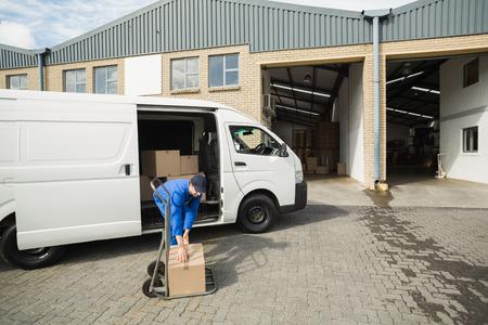 Livreur emballage sa camionnette dans un grand entrepôt Banque d'images