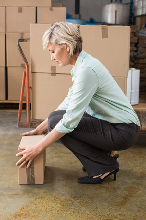 carrying box: Warehouse manager picking up cardboard box in a large warehouse Stock Photo