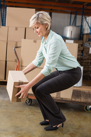 distribution box: Warehouse manager picking up cardboard box in a large warehouse Stock Photo