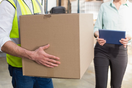 Close up of a warehouse worker carrying box in a large warehouse photo