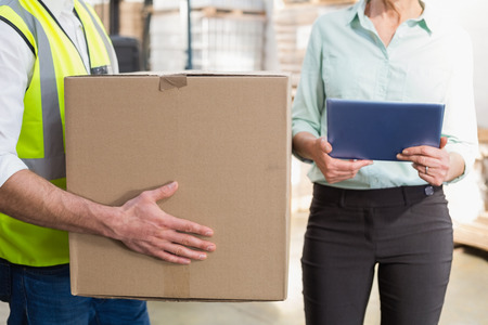 Worker carrying box with manager holding tablet pc in a large warehouse photo