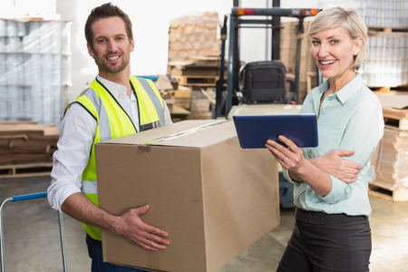 Warehouse manager and foreman working together in a large warehouse photo